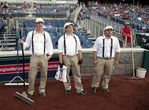 """Members of the Washington Nationals grounds crew wait for the start of a baseball game against the San Francisco Giants, Thursday, July 5, 2012, in Washington. For """"Turn Back the Clock Night"""" both teams wore replica uniforms from the 1924 World Series between the New York Giants and the Washington Senators. (AP Photo/Evan Vucci)"""