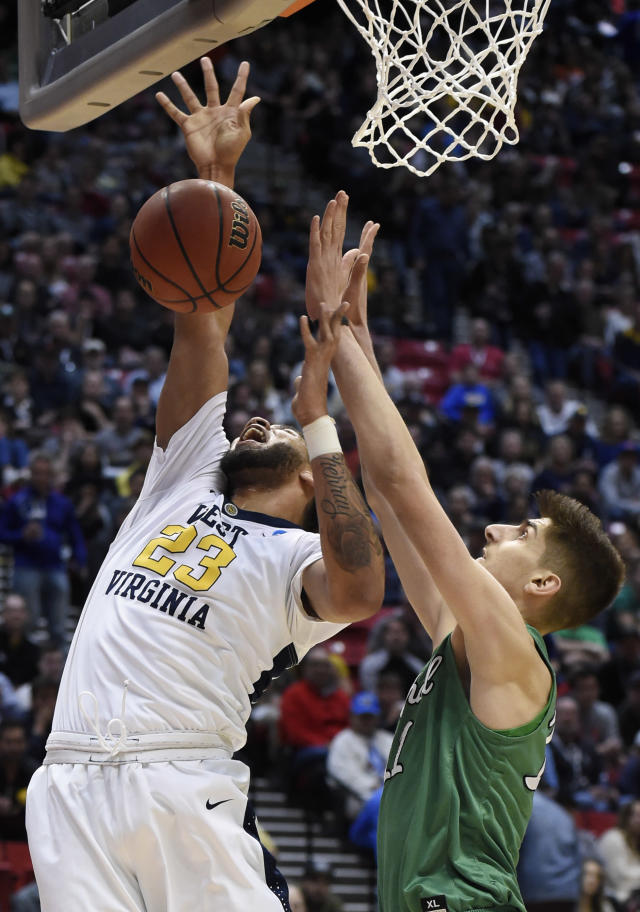 West Virginia forward Esa Ahmad (23) tries to shoot as Marshall forward Ajdin Penava (11) defends during the first half of a second-round NCAA college basketball tournament game Sunday, March 18, 2018, in San Diego. (AP Photo/Denis Poroy)
