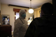 Doctor Luigi Cavanna and his nurse assistant Gabriele Cremona visit a patient in Piacenza, Italy, Wednesday, Dec. 2, 2020. Italy recorded another 814 deaths on Friday, Dec. 4, 2020 as the toll from the COVID-19 resurgence remained stubbornly high, bringing Italy's pandemic total to 58,842. That is the second-highest death toll in Europe, behind Britain. (AP Photo/Antonio Calanni)