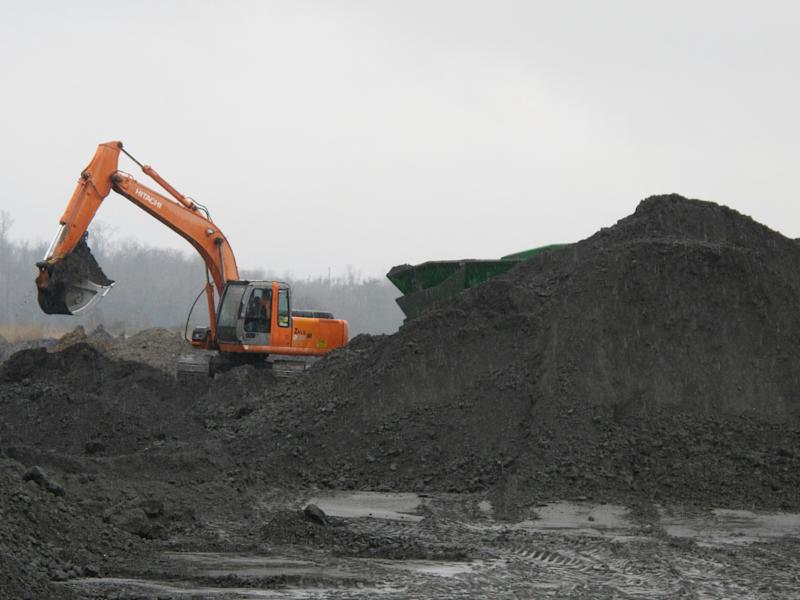 An excavator removes coal ash from the ash pond at Santee Cooper's Jefferies power generating station just outside Moncks Corner, S.C., on Feb. 26, 2014. The recycled coal ash is trucked from the site and then used in the manufacture of concrete. Santee Cooper is South Carolina's state-owned electric and water utility. (AP Photo/Bruce Smith)
