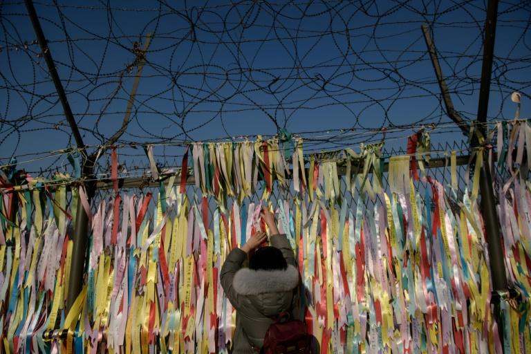 A woman hangs a 'peace ribbon' on a fence at the Imjingak 'peace park' near the Demilitarized Zone (DMZ) separating the two Koreas -- South Korean President Moon Jae-in spoke with US leader Donald Trump after the North's latest weapons test (AFP Photo/Ed JONES)