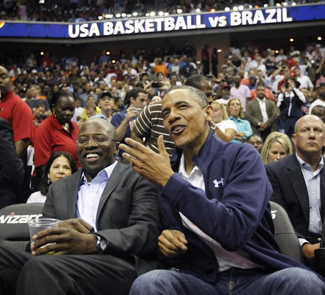 President Barack Obama, right, talks with his former personal aide Reggie Love, left, as they attend an Olympic men's exhibition basketball game between Brazil and Team USA in Washington, Monday, July 16, 2012. (AP Photo/Pablo Martinez Monsivais)