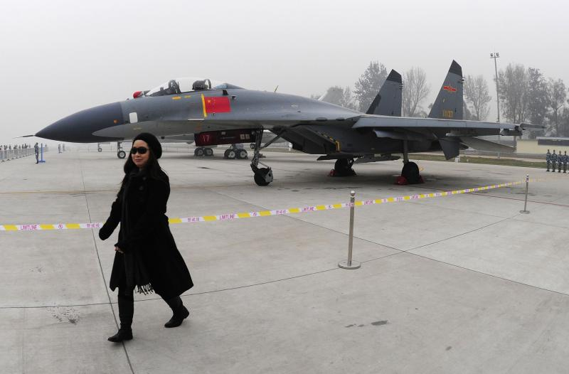 FILE - In this Nov. 8, 2009, file photo, a woman walks near a Chinese People's Liberation Army Air Force's J-11 fighter jet displayed for the Air Force's 60th anniversary at an airport in Beijing, China. Taiwan says its planes warned off Chinese military aircraft that crossed the center line in the Taiwan Strait, calling China's move a provocation that seeks to alter the status quo in the waterway dividing the island from mainland China.(AP Photo, File)
