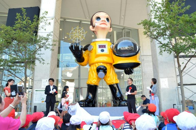 """Sun Child"", a 6.2-metre (20-foot) figure sporting a yellow protective suit with a digital display on its chest showing ""000"" -- symbolising no nuclear contamination -- was installed this month in  Fukushima, sparking criticism"