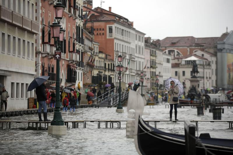 A woman standing on catwalk, right, set up on the occasion of a high tide takes pictures, in a flooded Venice, Italy, Tuesday, Nov. 12, 2019. The high tide reached a peak of 127cm (4.1ft) at 10:35am while an even higher level of 140cm(4.6ft) was predicted for later Tuesday evening. (AP Photo/Luca Bruno)