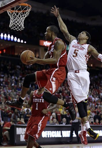 North Carolina State guard Lorenzo Brown, center, shoots past Maryland guard Nick Faust in the first half of an NCAA college basketball game in College Park, Md., Wednesday, Jan. 16, 2013. (AP Photo/Patrick Semansky)