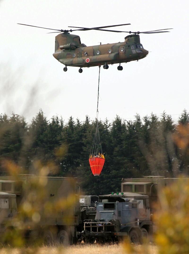 Japan's Self-Defense Forces's helicopter heads to the Fukushima Dai-ichi nuclear power plant to dump water on the stricken reactor in Okumamachi Thursday morning, March 17, 2011. (AP Photo/Asahi Shimbun, Masaru Komiyaji) JAPAN OUT, NO SALES, MANDATORY CREDIT