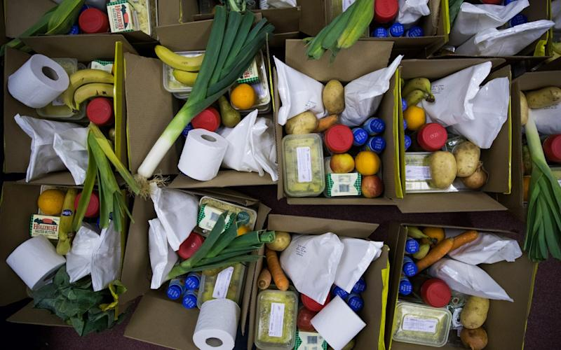 Boxes of food and toiletries sit on the floor waiting to be collected from the food bank run by Dads House charity in London - Chris Ratcliffe/Bloomberg