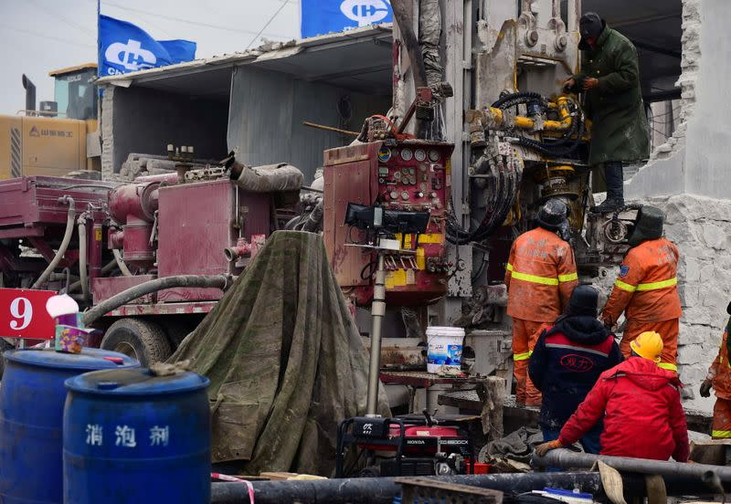 Rescuers work on saving workers trapped underground after an explosion at the Hushan gold mine in Qixia