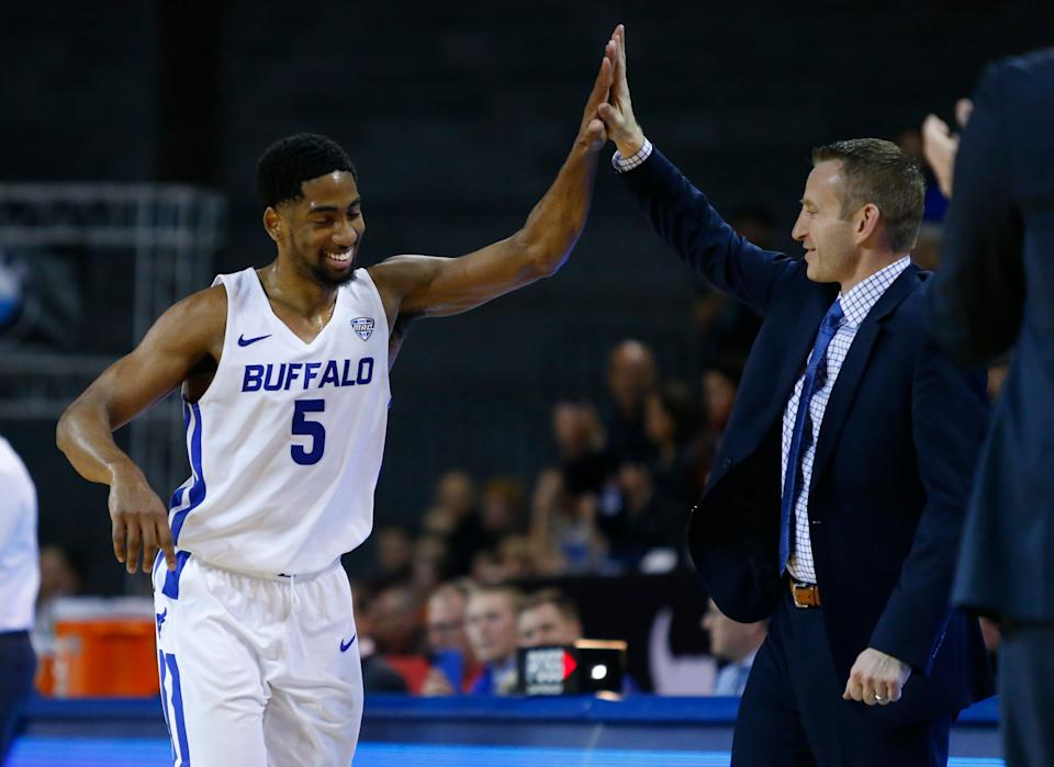 Buffalo guard CJ Massinburg (5) and head coach Nate Oats high five during the second half of an NCAA college Basketball game against Bowling Green, Friday, March 8, 2019, in Buffalo N.Y. (AP Photo/Jeffrey T. Barnes)