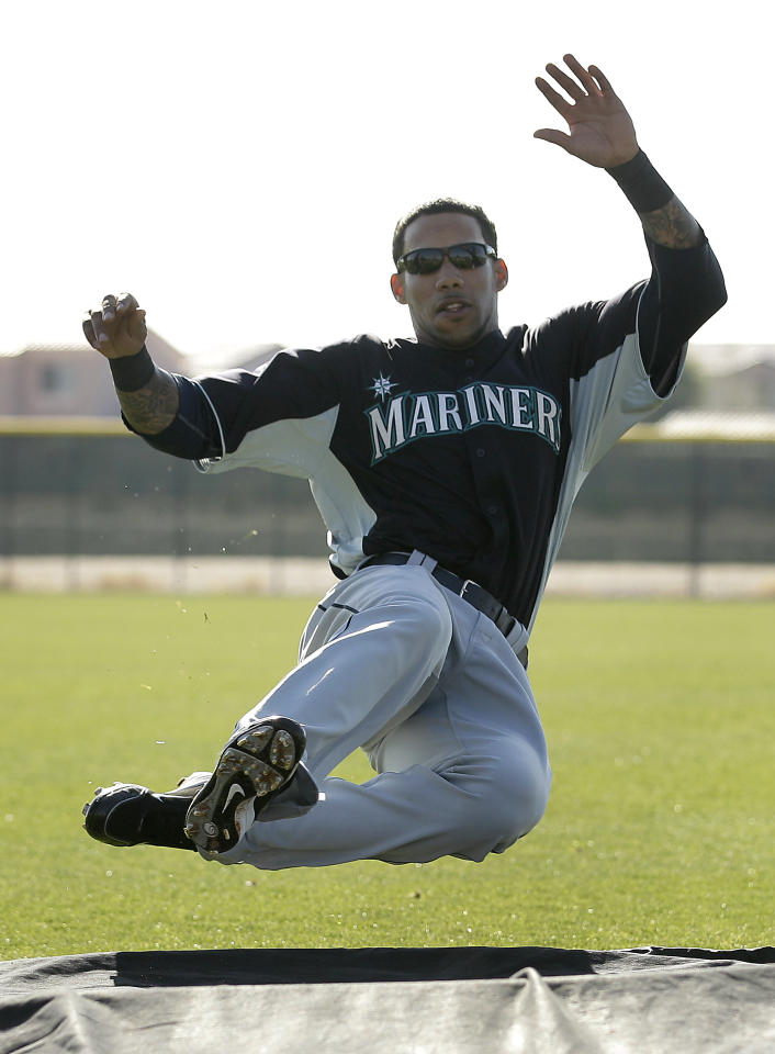 FILE - In this Feb. 24, 2011 file photo, Seattle Mariners baseball player Greg Halman practices sliding during baseball spring training in Peoria, Ariz. Greg Halman was stabbed to death early Monday, Nov. 21, 2011 in Rotterdam, Netherlands, and his brother was arrested as a suspect, Dutch police said. (AP Photo/Charlie Riedel, File)