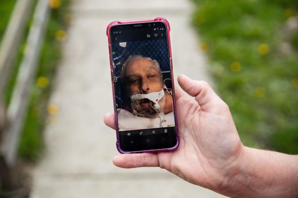 Ohio woman Christine Bevington holds a photo of her stepfather as they said goodbye on a video call before. he passed away from COVID-19 last month. Source: Getty