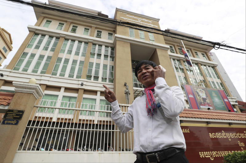 Journalist Uon Chhin talks on his smartphone upon arrival at the municipal court in Phnom Penh, Cambodia, Friday, Aug. 9, 2019. Two Cambodian journalists who had worked for U.S. government-funded Radio Free Asia were back on trial Friday on espionage charges that rights groups have characterized as a flagrant attack on press freedom. Uon Chhin and Yeang Sothearin are charged with undermining national security by supplying information to a foreign state, which is punishable by up to 15 years in prison. (AP Photo/Heng Sinith)
