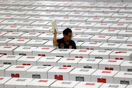 A worker carries election materials as he prepares ballot boxes in a warehouse in Jakarta