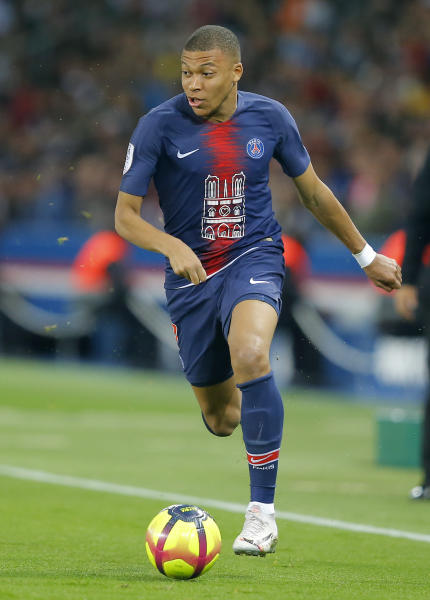 PSG's Kylian Mbappe runs with the ball during the French League One soccer match between Paris-Saint-Germain and Monaco at the Parc des Princes stadium in Paris, Sunday April 21, 2019. (AP Photo/Michel Euler)