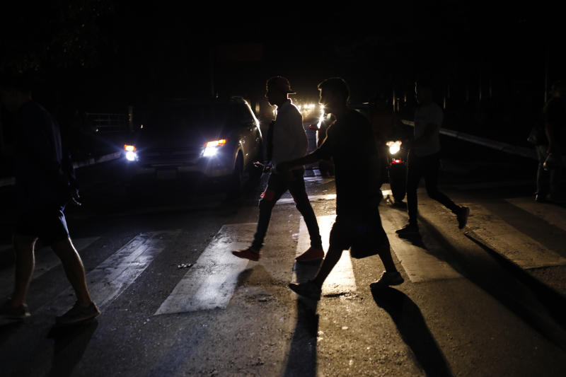 """FILE - In this Monday, July 22, 2019, file photo, people walk on a street during a blackout in Caracas, Venezuela. When much of Venezuela was plunged into darkness after a massive blackout earlier in the week, Maduro blamed the power outage on an """"electromagnetic attack"""" carried out by the United States. (AP Photo/Ariana Cubillos, File)"""