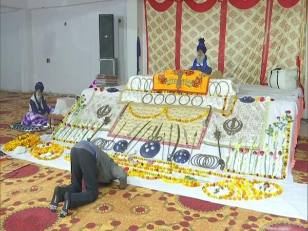 A protestor praying at the temporary Gurudwara at the Singhu border. (Photo/ANI)