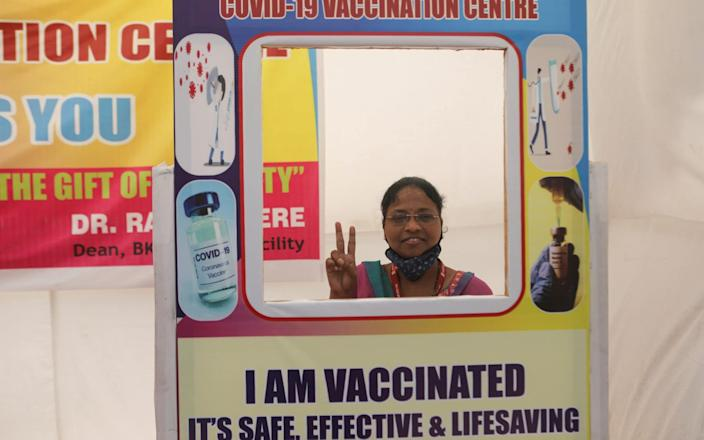 A woman poses after receiving a dose of Covishield vaccine - Reuters