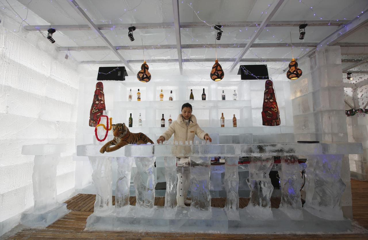 A waitress arranges ice cups on an ice counter during a photo opportunity at the Ice Palace in Shangri-La Hotel in the northern city of Harbin, Heilongjiang province January 6, 2014. The Ice Palace, which is built by ice bricks, is open annually from December to February and attracts visitors during the Harbin Ice and Snow Festival. The temperatures inside the ice building is maintained around -10 degrees Celsius and it consists of bar and hot pot restaurant. REUTERS/Kim Kyung-Hoon (CHINA - Tags: SOCIETY ENVIRONMENT TRAVEL)