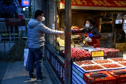 A vendor and customer wearing facemasks as a preventive measure against the novel coronavirus interact at a fruit and vegetable store in Beijing