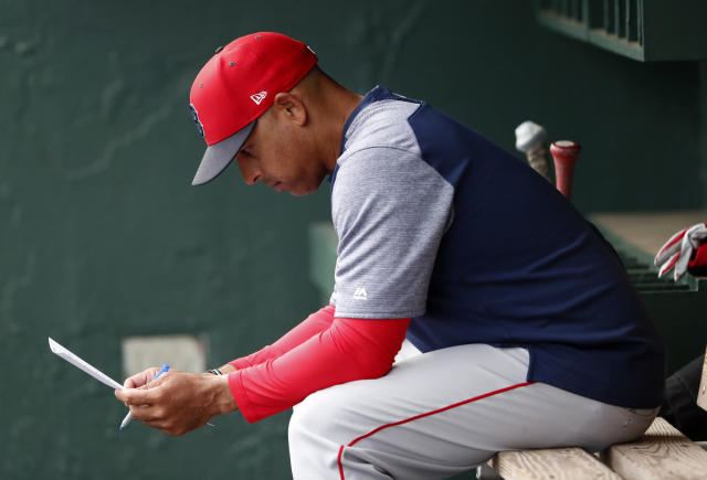 FILE - In this March 20, 2019, file photo, Boston Red Sox manager Alex Cora looks over the lineup before the team's spring training baseball game against the Baltimore Orioles in Sarasota, Fla. Cora was fired by the Red Sox on Tuesday, Jan. 14, 2020, a day after baseball Commissioner Rob Manfred implicated him in the sport's sign-stealing scandal. (AP Photo/John Bazemore)