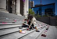 <p>Delhia Nahanee, of the Squamish Nation, places a rose on one of 215 pairs of children's shoes on the steps of the Vancouver Art Gallery as a memorial to the 215 children whose remains have been found buried at the site of a former residential school in Kamloops, in Vancouver, on Friday, May 28, 2021. Chief Rosanne Casimir of the Tk'emlups te Secwépemc First NationFirst Nation said in a news release Thursday that the remains were confirmed last weekend with the help of a ground-penetrating radar specialist. THE CANADIAN PRESS/Darryl Dyck</p>