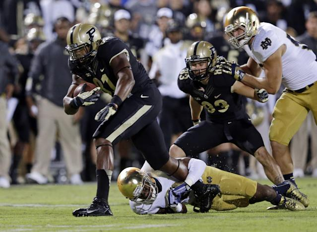 Purdue wide receiver Bilal Marshall, left, is tackled by Notre Dame cornerback KeiVarae Russell after picking up 14 yards during the first half of an NCAA college football game in West Lafayette, Ind., Saturday, Sept. 14, 2013. (AP Photo/Michael Conroy)