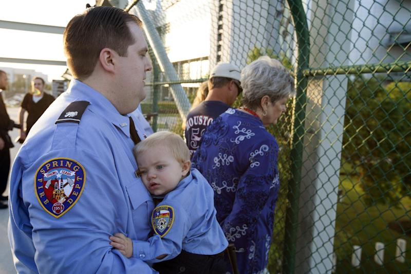 Bradley Vass holds a fellow firefighter friends child , 8-month old Nolan Hurl, before the Firefighter's memorial procession Wednesday, June 5, 2013 in Houston. As many as 40,000 people are expected to remember the four firefighters who died Friday, the deadliest day in the Houston Fire Department's 118-year history. Killed in the fire when the motel structure collapsed were Capt. Matthew Renaud, 35, engineer operator Robert Bebee, 41, firefighter Robert Garner, 29, and Anne Sullivan, 24, a probationary firefighter who had graduated in April from the Houston Fire Department Academy. (AP Photo/Michael Stravato)