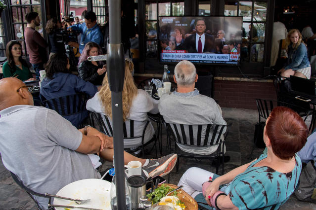 <p>Spectators and patrons at Shaw's Tavern in northwest Washington watch as former FBI Director James Comey is sworn in to testify before the Senate Intelligence Committee on June 8, 2017. (Photo: Jim Watson/AFP/Getty Images) </p>