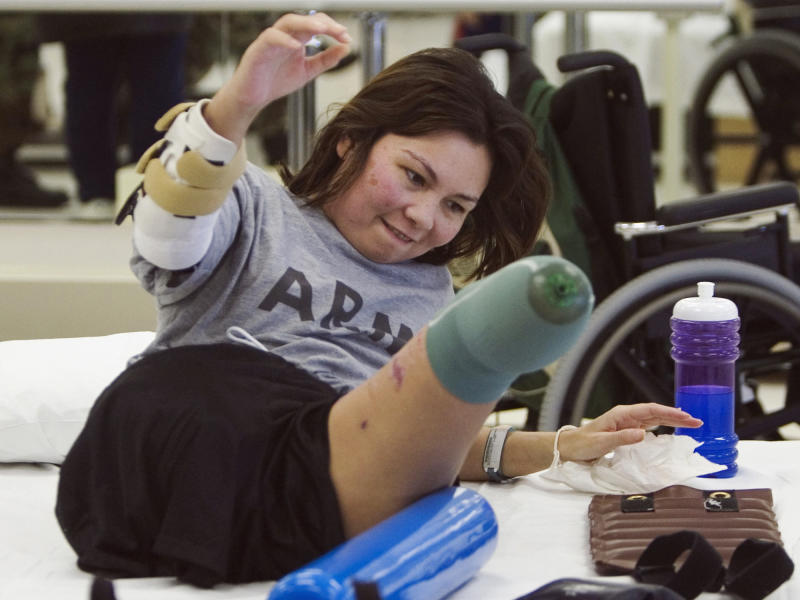 FILE - In this Jan. 31, 2005, file photo, Army Major Tammy Duckworth rolls herself up during physical therapy at the Walter Reed Army Medical Center in Washington. Duckworth lost both legs when the helicopter she was in was struck by a rocket-propelled grenade during a mission near Baghdad on Nov. 12, 2004. (AP Photo/The Arizona Republic, Michael Chow)