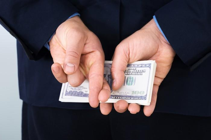 A businessman in a suit holding a pile of cash behind his back with his fingers crossed.