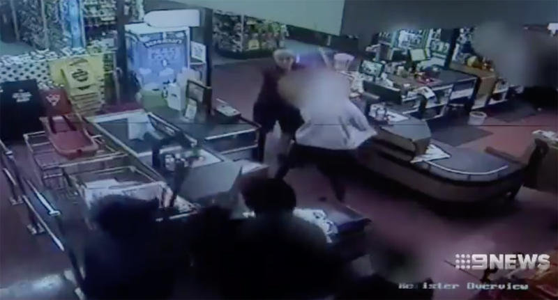 Security camera vision shows the staff member fighting off several youths attacking him with broomsticks.
