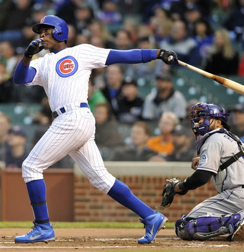 Chicago Cubs' Alfonso Soriano watches his two-run home run as the Colorado Rockies' Wilin Rosario looks on during the first inning of a baseball game Monday, May 13, 2013, in Chicago. (AP Photo/Jim Prisching)