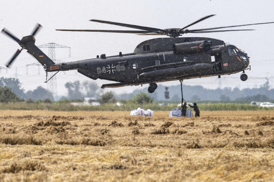 A Bundeswehr CH-53 transport helicopter picks up big bags of ballast in Ergfstadt, Germany, Thursday July 22, 2021, to fly them to the Blessem district to damn up the banks of the Erft river. In the flood disaster area of Erftstadt-Blessem, some residents are being allowed back into their homes to clear debris after heavy rains caused devastating floods. (Marius Becker/dpa via AP)