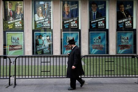 A man walks past posters of Fox News personalities including Gretchen Carlson at the News Corporation headquarters building in New York