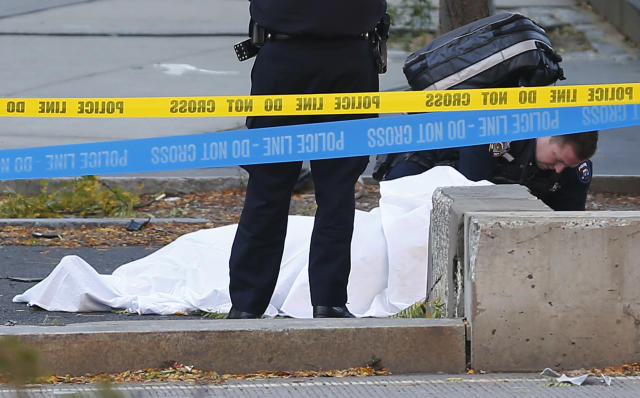 <p>A paramedic looks at a body covered under a white sheet along the bike path on Oct. 31, 2017, in New York City. (Photo: Bebeto Matthews/AP) </p>