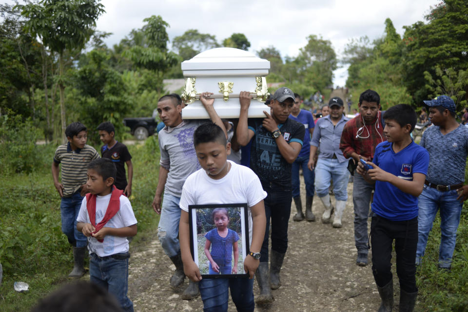 A boy carries a photo of Guatemalan 7-year-old Jakelin Caal Maquin, who died two days after being taken into custody by the U.S. Border Patrol, as her coffin is carried to the cemetery on Dec. 25, 2018. (Photo: Johan Ordonez/AFP/Getty Images)