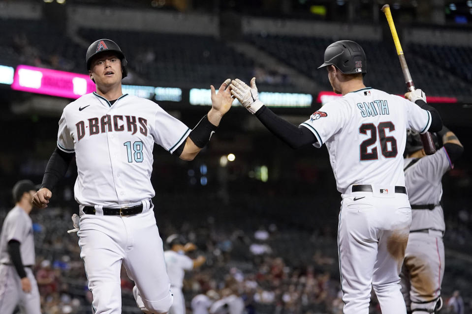 Arizona Diamondbacks' Carson Kelly (18) and Pavin Smith (26) celebrate after scoring on a double hit by David Peralta during the fifth inning of a baseball game against the Miami Marlins, Tuesday, May 11, 2021, in Phoenix. (AP Photo/Matt York)