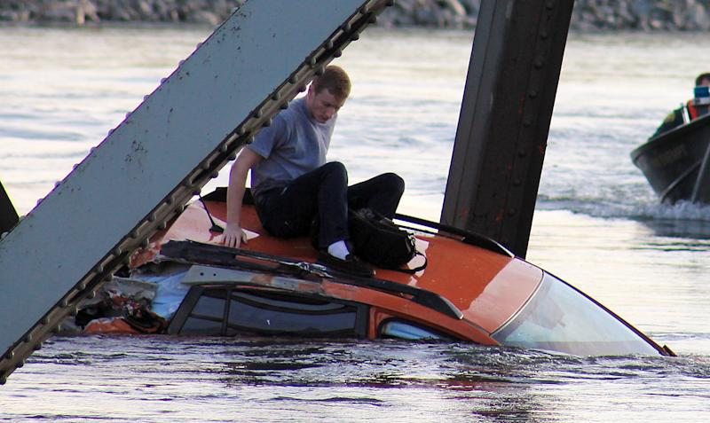 In this photo provided by Francisco Rodriguez, a man is seen sitting atop a car that fell into the Skagit River after the collapse of the Interstate 5 bridge there minutes earlier Thursday, May 23, 2013, in Mount Vernon, Wash. (AP Photo/Francisco Rodriguez)