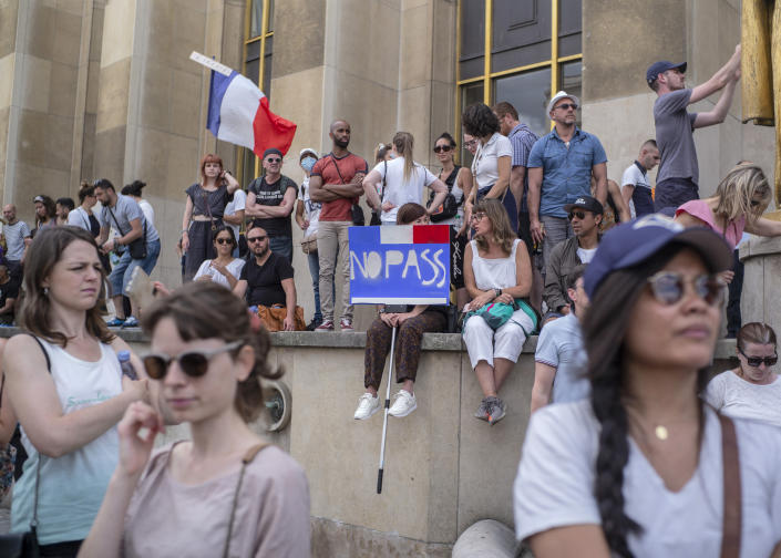 People attend a demonstration in Paris, France, Saturday 24, 2021, against the COVID-19 pass which grants vaccinated individuals greater ease of access to venues (AP Photo/Rafael Yaghobzadeh)