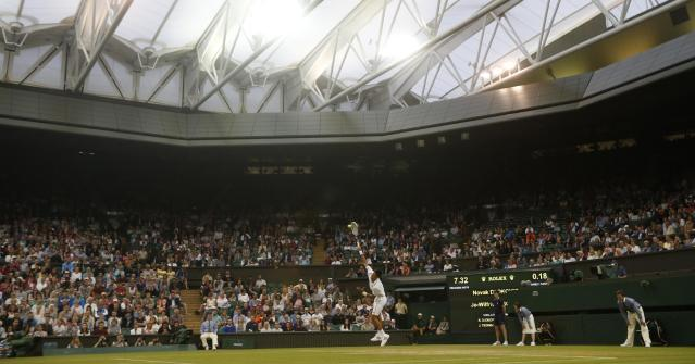 Novak Djokovic of Serbia serves to Jo-Wilfried Tsonga of France during their men's singles match at the All England Lawn Tennis Championships in Wimbledon, London, Monday, June 30, 2014. The match is being played on Centre Court under the roof due to the weather.(AP Photo/Pavel Golovkin)