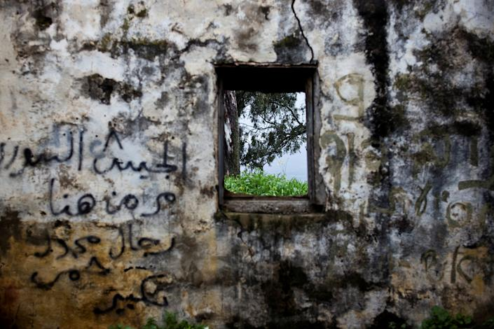 """The wall of a structure is seen in a former Syrian outpost in the Israeli-occupied Golan Heights, the territory that Israel captured from Syria in the 1967 Six Day War, Feb. 27, 2019. In stark contrast to the beauty of the surrounding countryside, it is now crumbling and covered in graffiti. One Arabic message reads: """"The Syrian army passed by here."""" (Photo: Ronen Zvulun/Reuters)"""