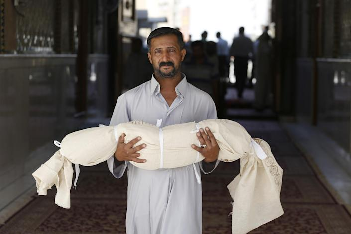 FILE - In this Tuesday, Sept. 24, 2013 file photo, Qasim Ahmed Tahan carries the dead body of his 5-year-old son, Walid, who was killed in a bombing on Monday, before burial in the Shiite holy city of Najaf, 100 miles (160 kilometers) south of Baghdad, Iraq, Tuesday, Sept. 24, 2013. Al-Qaida has come roaring back in Iraq since U.S. troops left in late 2011 and now looks stronger than it has in years. The terror group is capable of carrying out mass-casualty attacks several times a month, driving the death toll in Iraq to the highest level in half a decade. It sees each attack as a way to maintain an atmosphere of chaos that weakens the Shiite-led government's authority.(AP Photo/Jaber al-Helo, File)