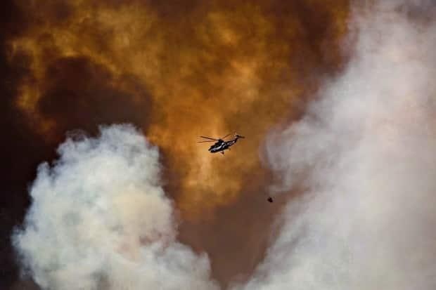 A helicopter battles a wildfire in Fort McMurray, Alta., on May 4, 2016. (Jason Franson/The Canadian Press - image credit)