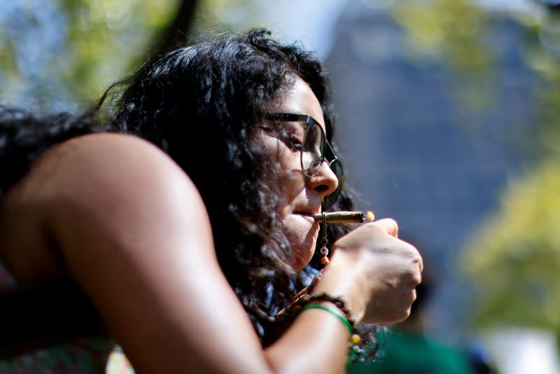 FILE PHOTO: An activist in favor of legalized marijuana lights a marijuana cigarette during a march as they wait for the Congress to pass a bill that would legalize it, in Mexico City