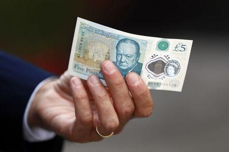Bank of England governor Carney poses with a new polymer five pound note at Whitecross Street Market in London