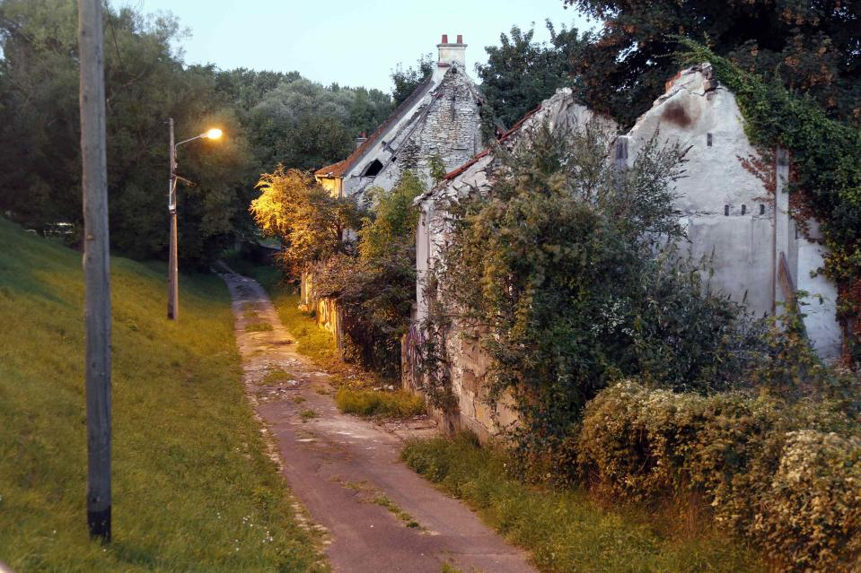 Overgrown trees and bushes in the deserted Gaudry street. The town's problems are traced back to the 1960s when plans for the Charles de Gaulle airport were finalised. The farming town was surrounded by acres of green space, perfect for an international airport. (Reuters)