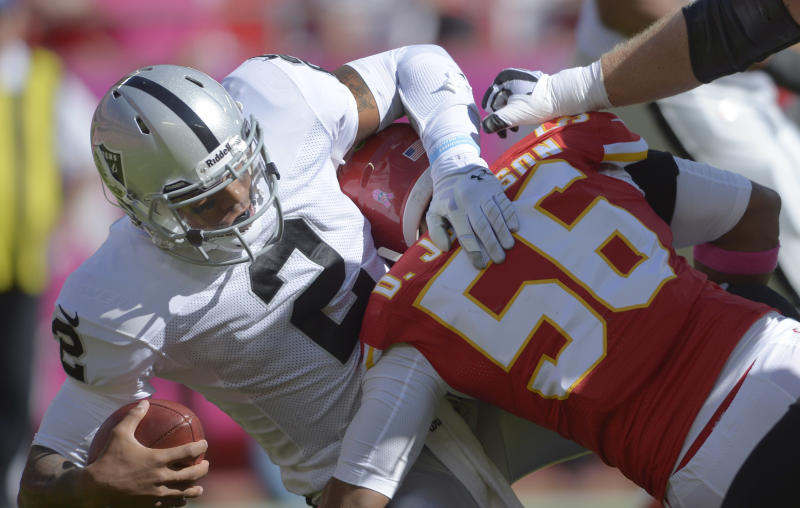 Oakland Raiders quarterback Terrelle Pryor (2) is tackled by Kansas City Chiefs inside linebacker Derrick Johnson (56) during the first half of an NFL football game at Arrowhead Stadium in Kansas City, Mo., Sunday, Oct. 13, 2013. (AP Photo/Reed Hoffmann)