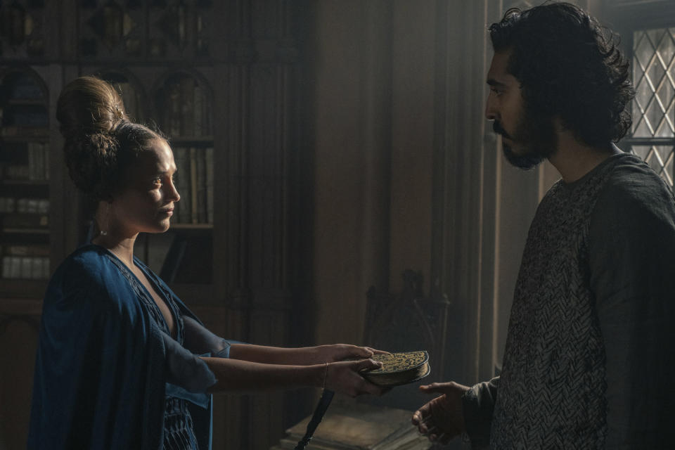 """This image released by A24 shows Alicia Vikander, left, and Dev Patel in a scene from """"The Green Knight."""" (Eric Zachanowich/A24 Films via AP)"""