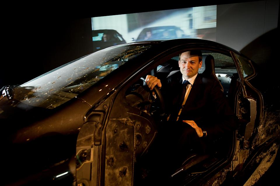 """Stunt driver Ben Collins sits in one of the Aston Martin DBS cars that he used in the James Bond film """"Quantum of Solace"""" at the press preview for the exhibition """"Bond in Motion"""" at the London Film Museum in central London on March 18, 2014. Including the iconic vhicles from the action franchise including the """"Wet Nellie"""" Lotus Esprit S1 from """"The Spy Who Loved Me"""" to Auric Goldfinger's Rolls Royce from """"Goldfinger"""", the exhibition opens to the public on March 21. AFP PHOTO/Leon Neal        (Photo credit should read LEON NEAL/AFP via Getty Images)"""